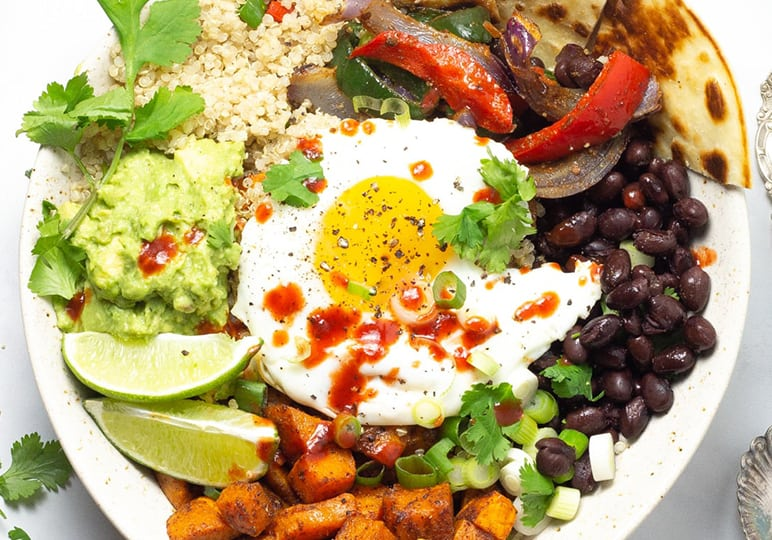 Quinoa, avocado, beans, egg, peppers and lime in a bowl