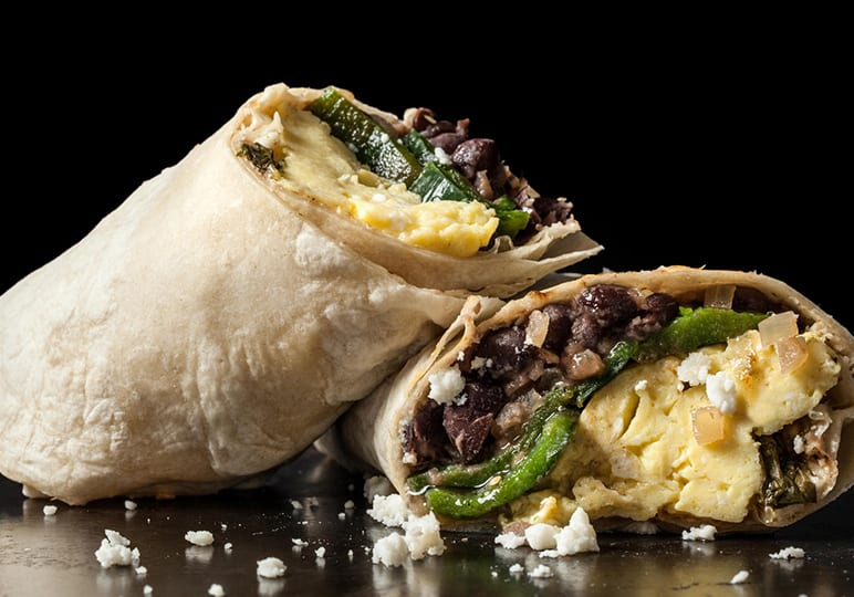 A burrito filled with beans peppers and eggs sliced in half