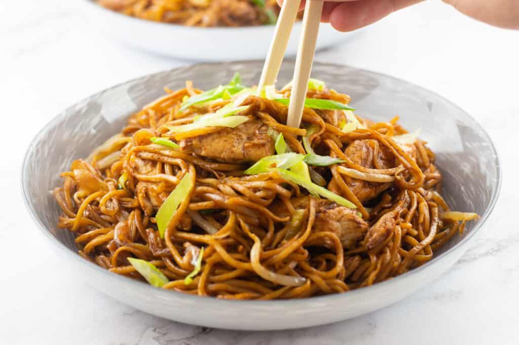 Chicken chow mein in a bowl with chopsticks