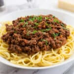 Slow Cooked Bolognese in a white bowl with spaghetti