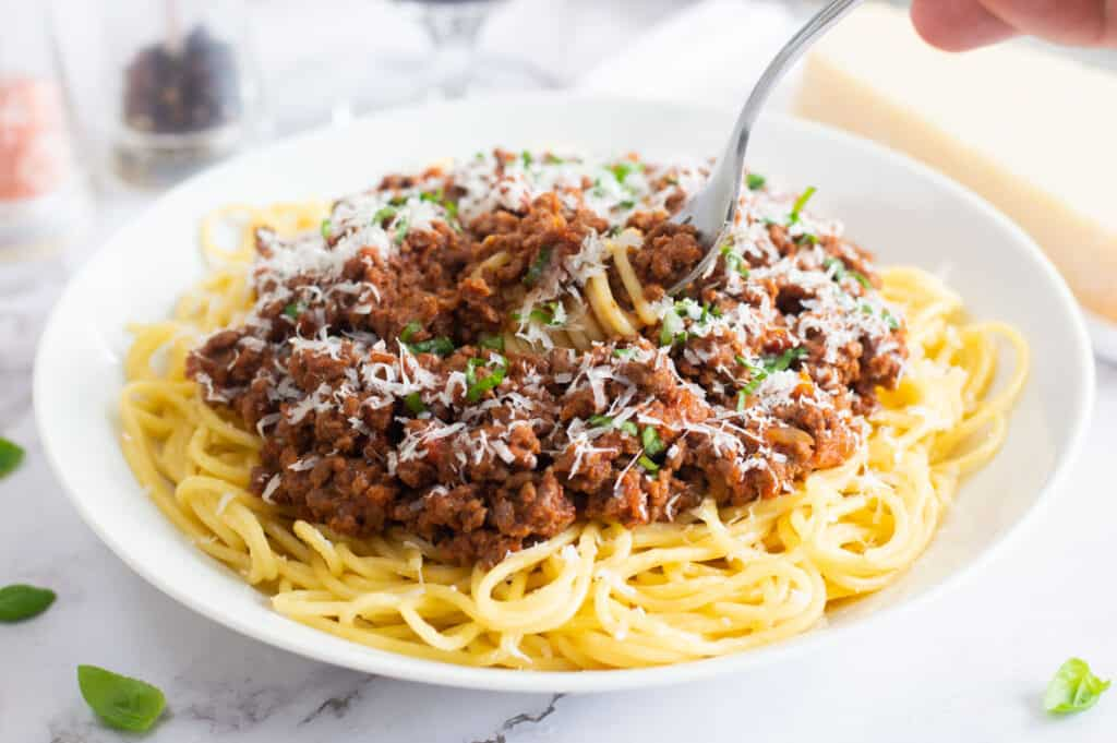 Spaghetti bolognese with grated parmesan and basil with a fork