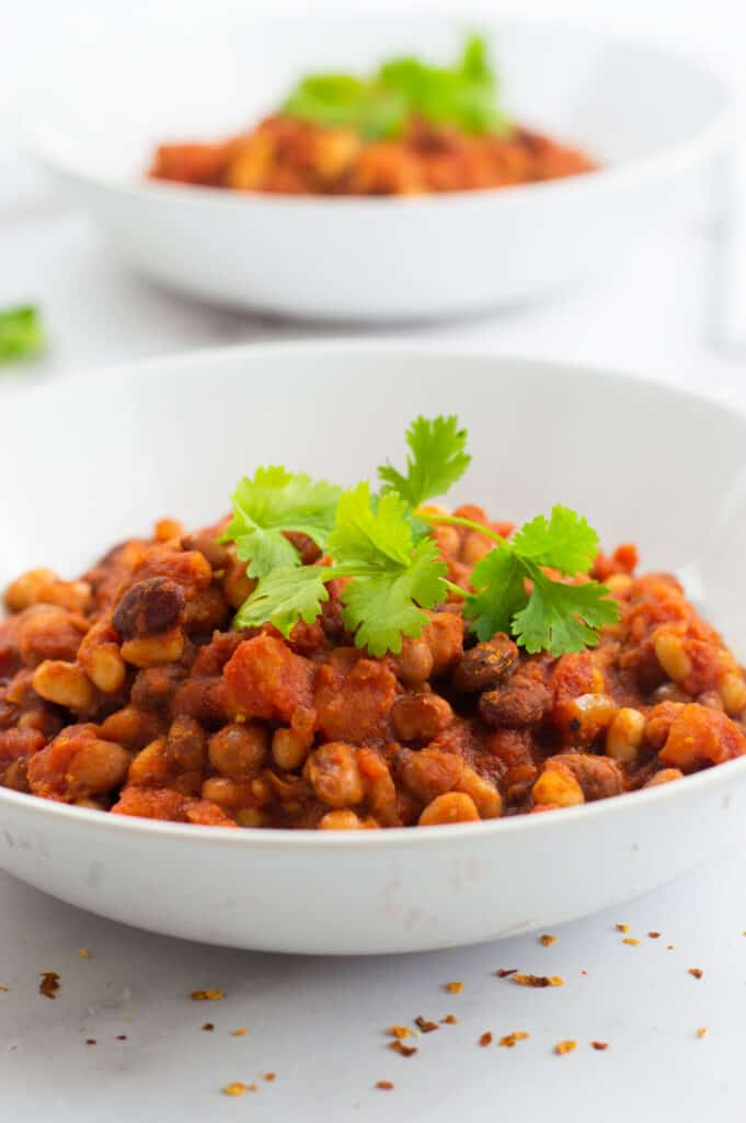 Two bowls of slow cooked chilli with herbs