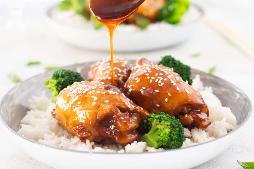 Pouring teriyaki glaze over chicken thighs with rice and broccoli