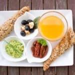 Bread, guacamole, fruit and orange juice