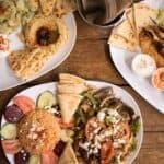 Greek salad, hummus, pitta breads, and dip on white plates