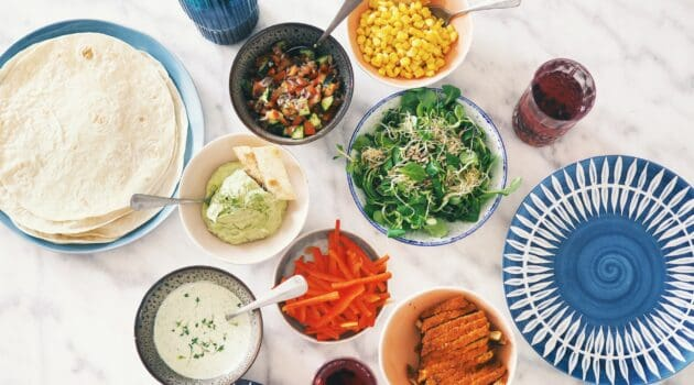 A range of small side dishes in small bowl like sweetcorn, greens, carrots and tortillas